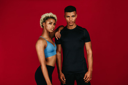 Fitness couple standing together on maroon background