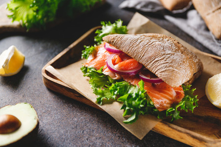 Healthy sandwich with rye bread bun  salmon  avocado  onion and salad served on a wooden rustic board