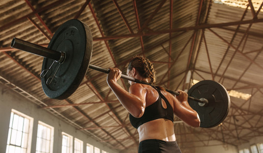 Strong woman exercising with barbell