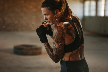 Female doing shadow boxing in empty factory shade