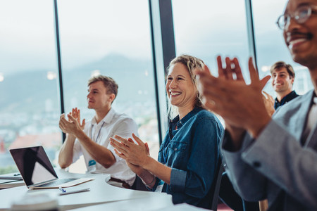 Business professionals clapping hands in conference