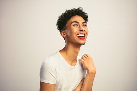 Feminine man wearing makeup laughing