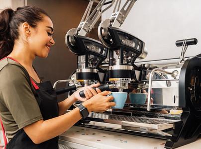 Female barista using a coffee