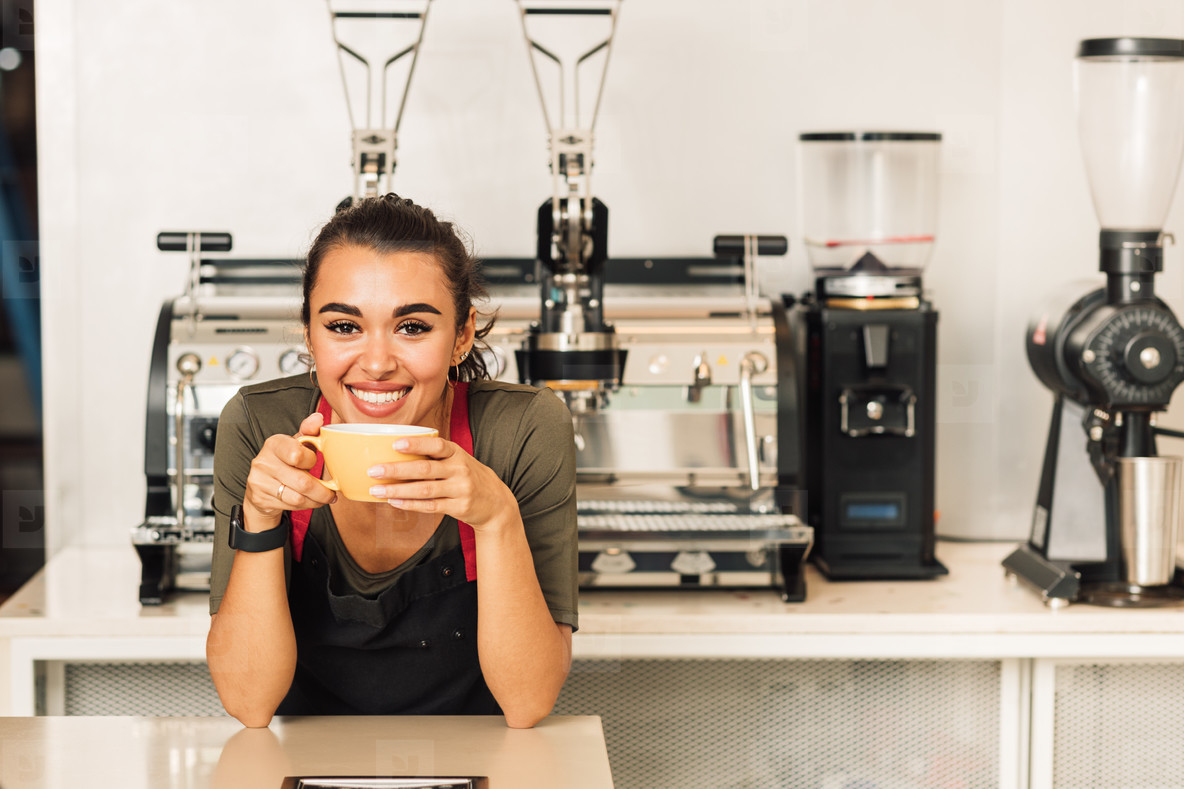 Smiling woman in apron leaning