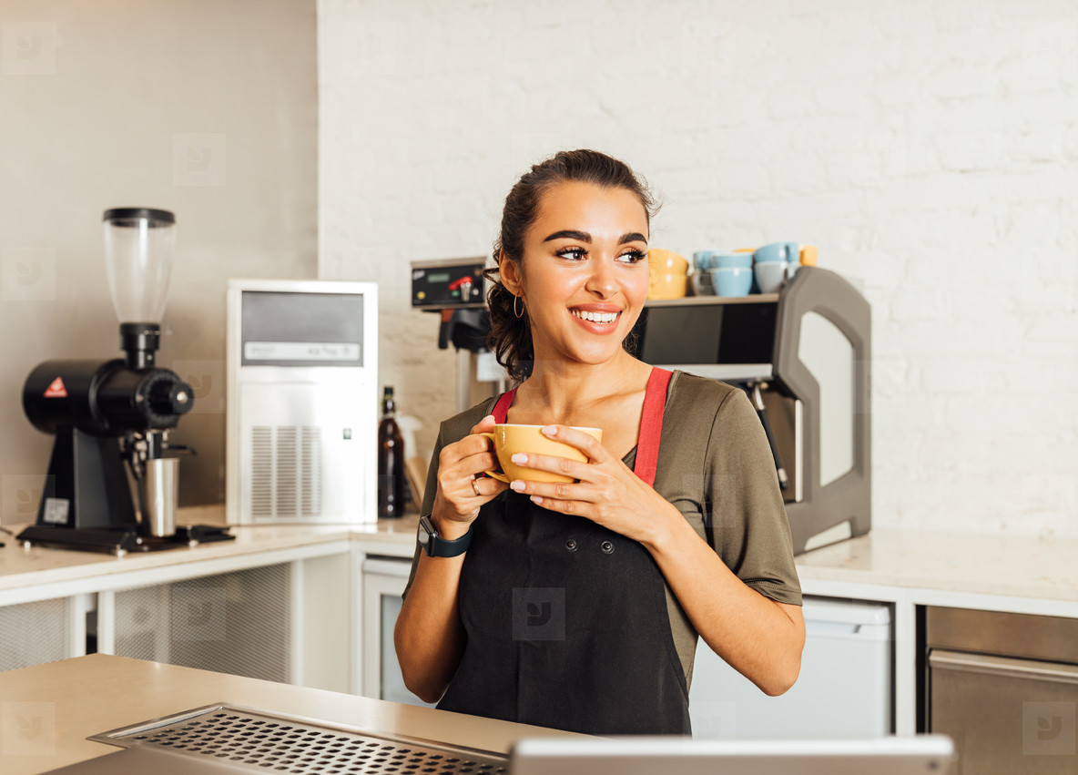 Smiling female barista looking