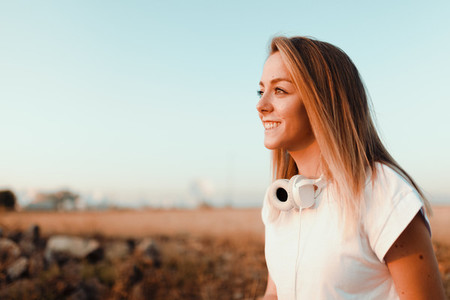Young woman watching sunset with her headphones on the field