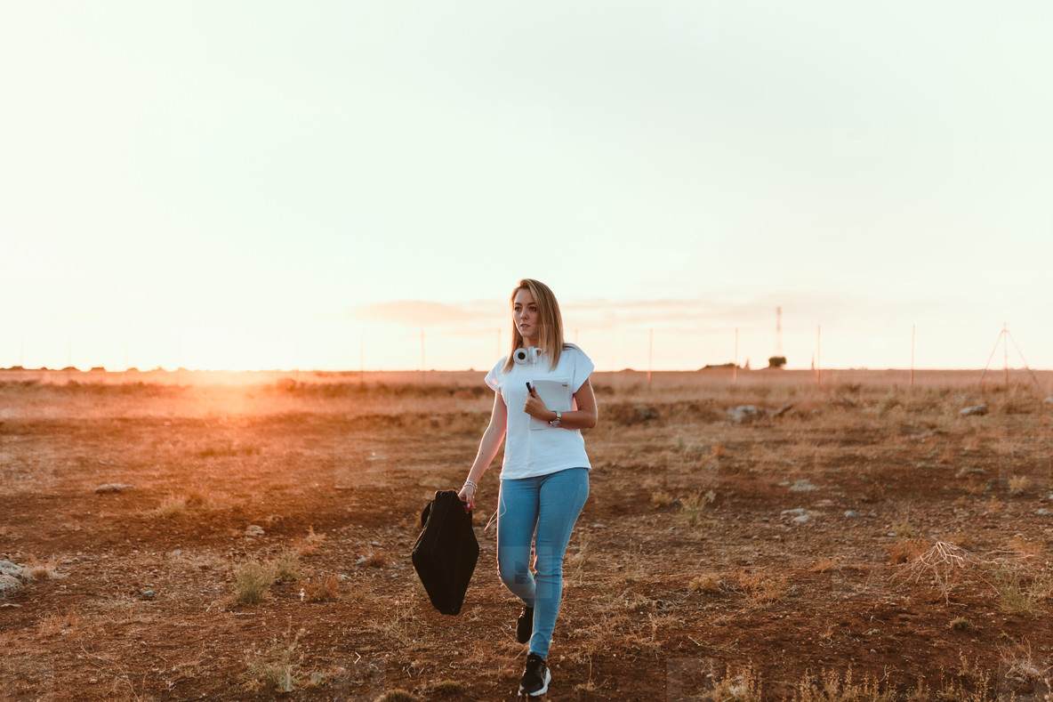 Young woman walking through the field with her laptop case