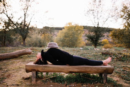 Woman practicing yoga and stretching lying down on a bench