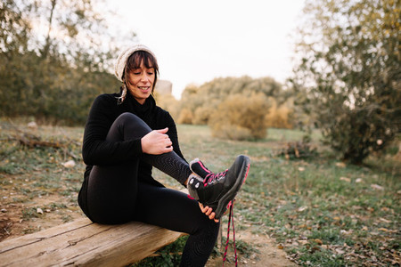 Woman hiker resting on the bench in park after trekking