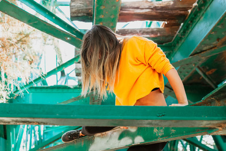 Woman climbing between iron beams of old railway bridge