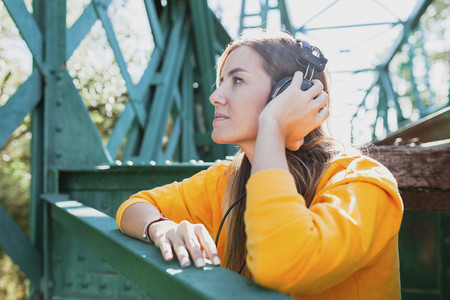 Woman listening to music with her old headphones on an abandoned iron bridge