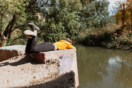 A woman lying near a river bank in autumn