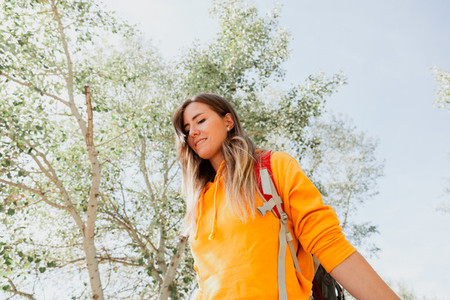 Smiling woman exploring old railroad tracks with her backpack and enjoying the surroundings