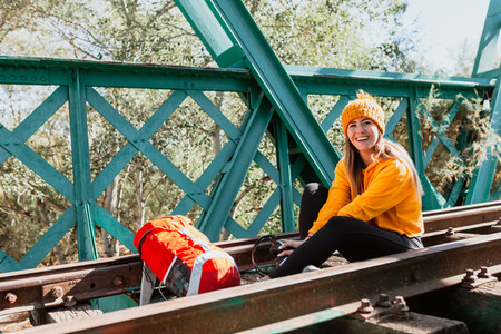 Woman trekking rests on an abandoned railway track