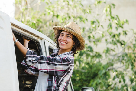 Young farmer woman in a van looking out at crop field