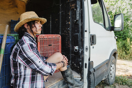 Young farmer woman resting in a van at crop field