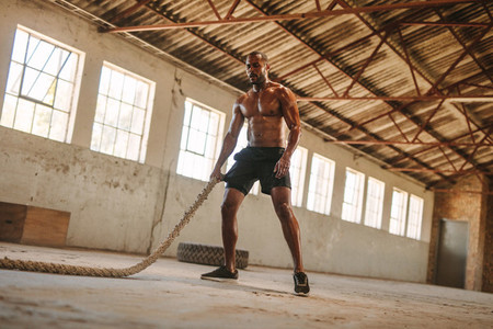 Muscular man working out in cross training gym