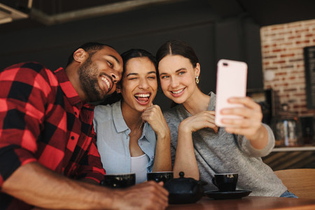 Diverse group of friends taking selfie at cafe