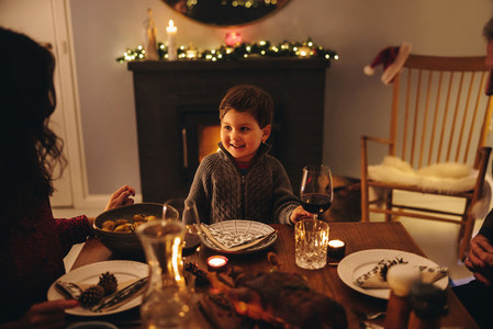Boy having Christmas dinner with family