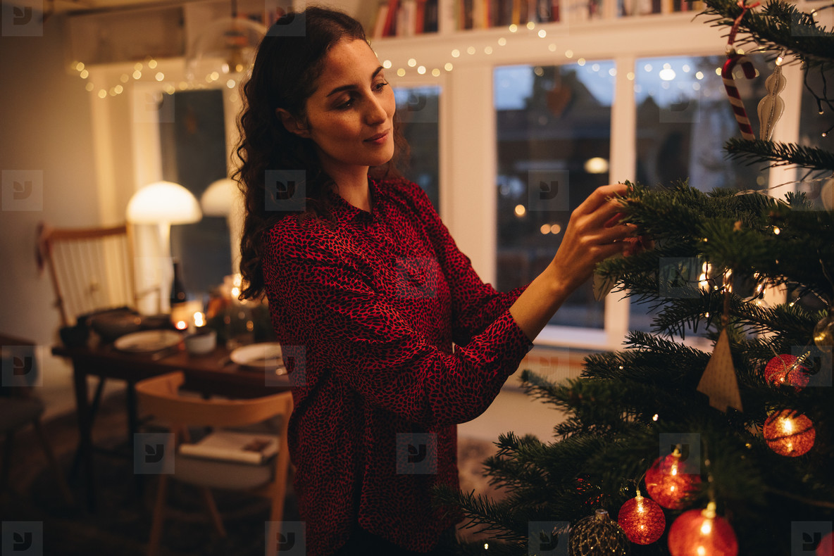 Woman hanging Christmas decorations on a tree