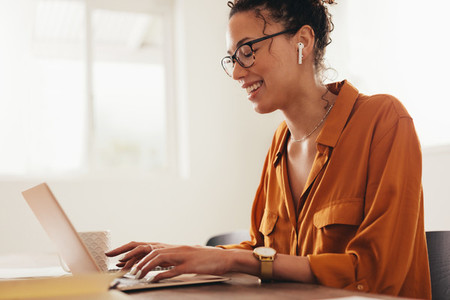 Woman blogger using laptop at home