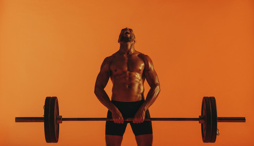 Muscular man training on lifting weights