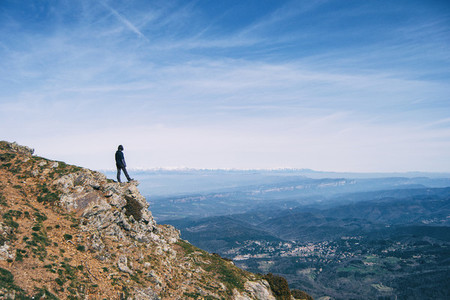 A girl contemplating the landscape from the top of a rock