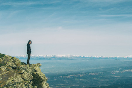 A girl on the top of a rock looking at the camera