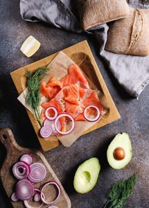 Ingredients for making healthy sandwich Rye bread bun salmon avocado onion dill and lemon Top view