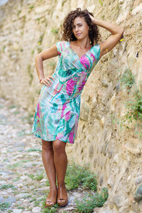 Beautiful brunette middle aged woman wearing spring colorful dress outdoors
