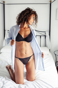 Middle aged woman In lingerie and shirt posing on the bed