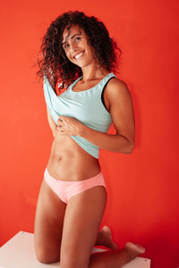 Middle aged woman posing wearing a blue t shirt and panties