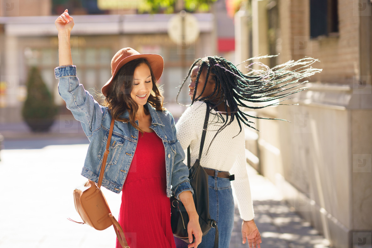 Two female dancing together on the street  Multiethnic friends