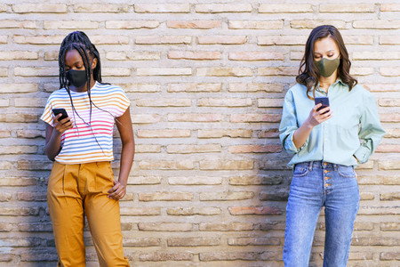 Multiethnic young women wearing masks using smartphone separated to respect social distance