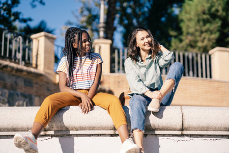 Two friends having fun together on the street sitting on a urban wall