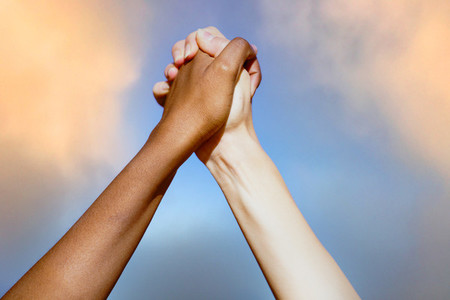 Multiethnic womens hands together against cloudy sky
