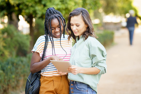 Two multiethnic women consulting something on a digital tablet