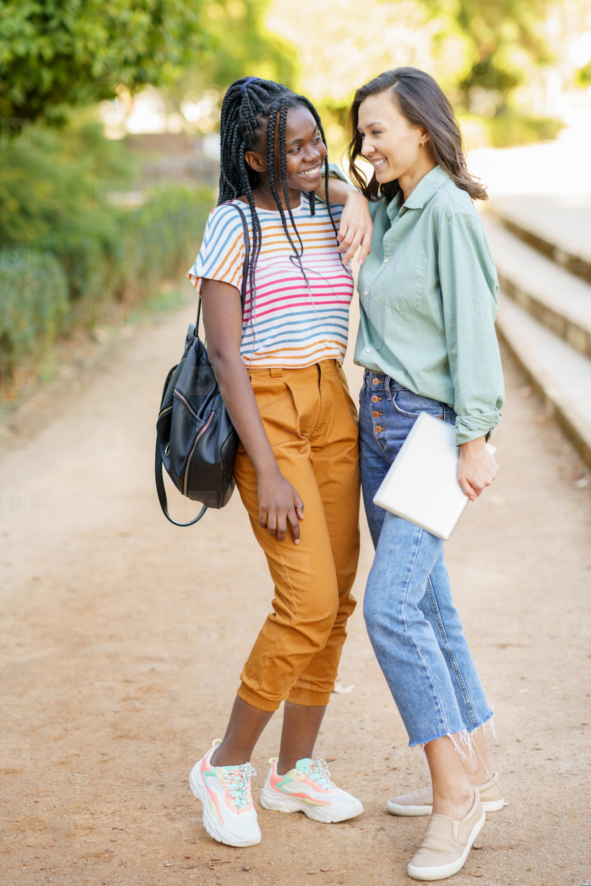 Two multiethnic girls posing together with colorful casual clothing