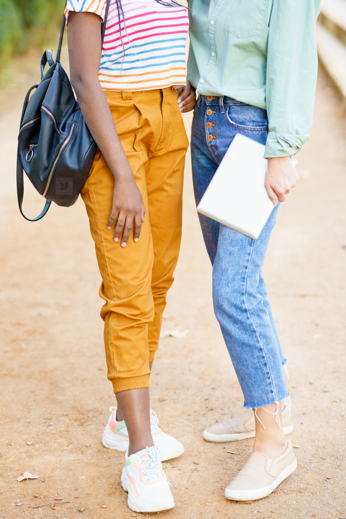 Two unrecognizable multiethnic girls posing together with colorful casual clothing