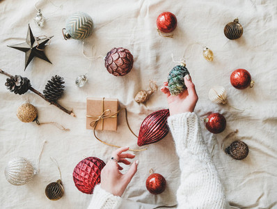 Christmas decoration toys and womans hands with pine cone