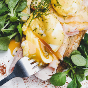 Poached eggs on bread with ham and salad  square crop