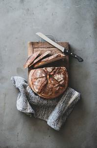 Freshly baked sourdough bread on wooden board  vertical composition