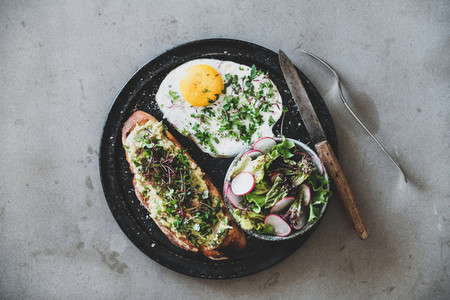 Healthy breakfast with avocado toast fried egg and green salad