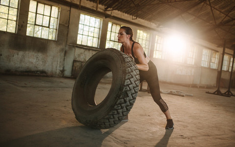 Fit woman doing tire flipping workout