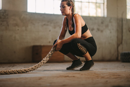 Woman taking rest after battle rope workout