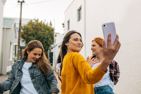 Woman taking a selfie with friends dancing