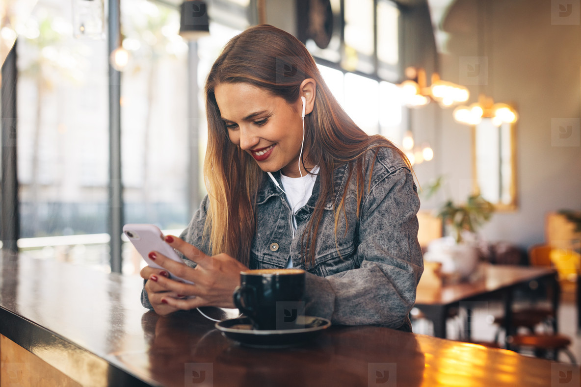 Woman in coffee shop listening to music from cell phone