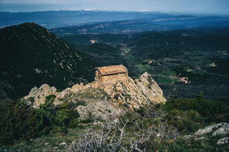 An old small stone house built on top of a rock on the heights