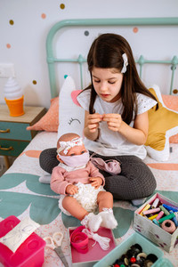Girl sewing face masks for herself and her baby doll