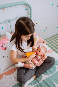 little girl playing feeding her baby doll